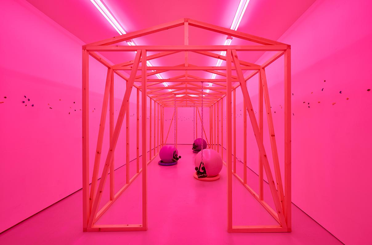 Anikó Kuikkas utställning på Gao Galleri i London. Konstruktioner i trä som bildar ett hus är centrerat i bilden och inuti den finns gymnastikbollar. Rummet är belyst med rosa.