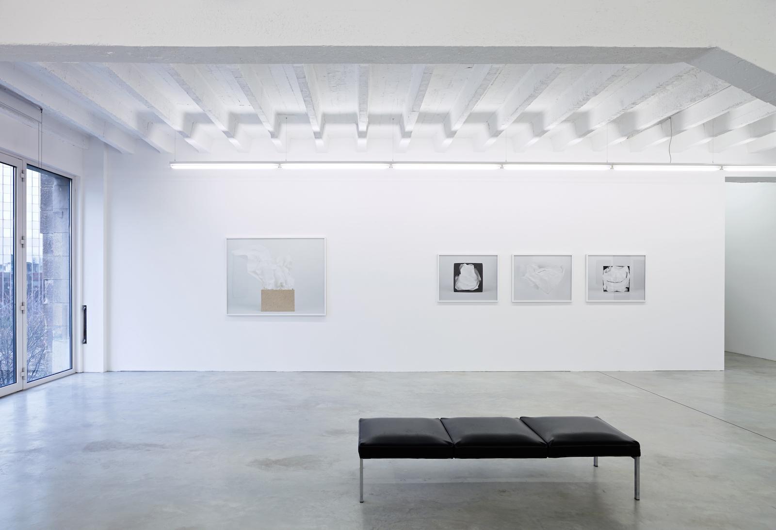 Bild från en utställning. Rummet är vitt och det finns fyra verk på väggen. Framför dem till höger i bilden är en svart bänk.