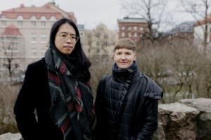 Kuvassa Christina Li, jolla pitkä musta tukka ja silmälasit sekä Pilvi Takala, jolla lyhyt ruskea tukka. Kuva on otettu ulkona ja taustalla näkyy korkeita kivirakennuksia.