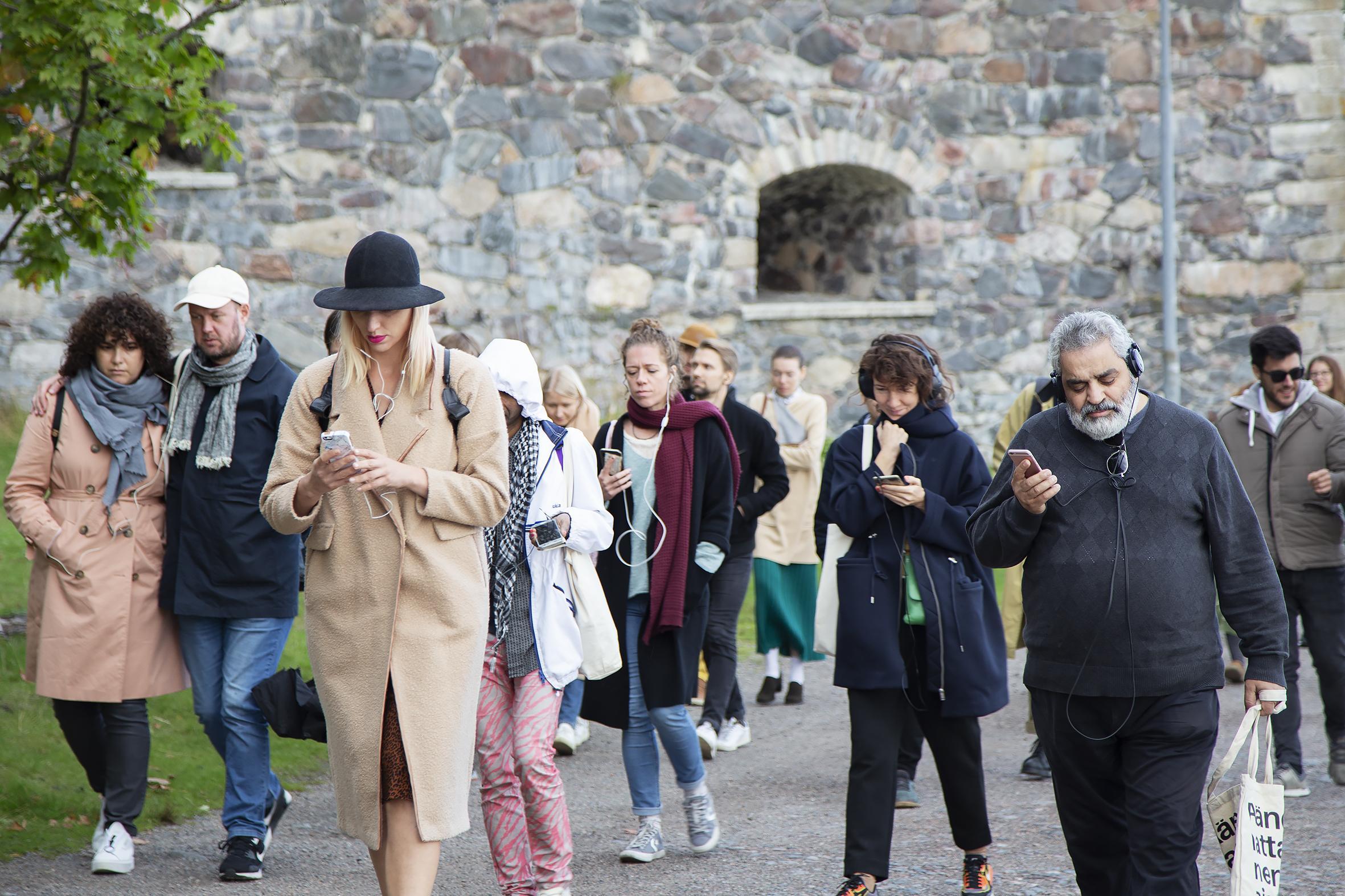 Joukko ihmisiä ulkona kävelemässä samaan suuntaan.