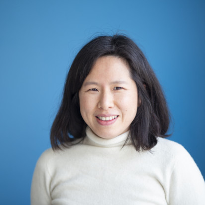 Woman with dark hair and white shirt in from of a blue background.