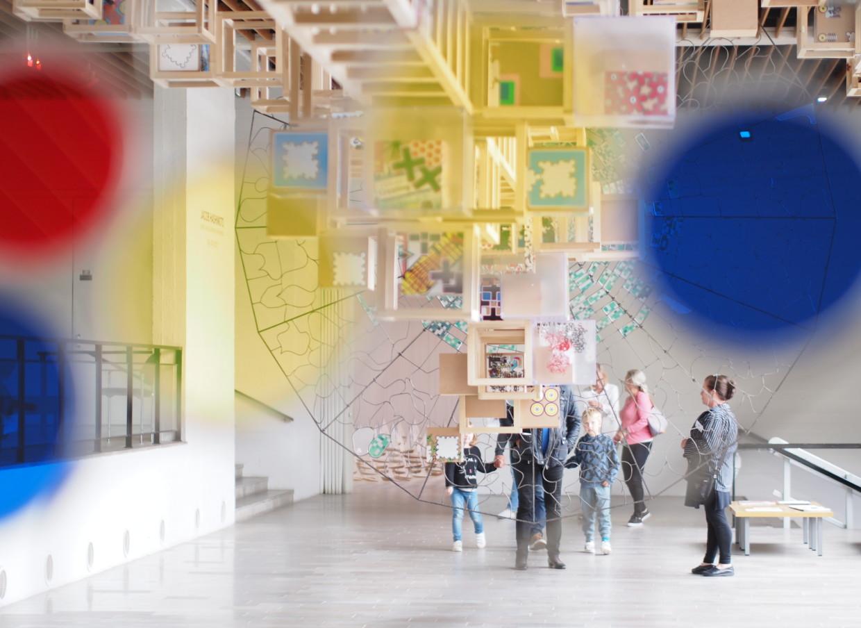 Värikkäitä ympyröitä lähikuvassa, joiden läpi heijastuu ihmisiä kaukana.