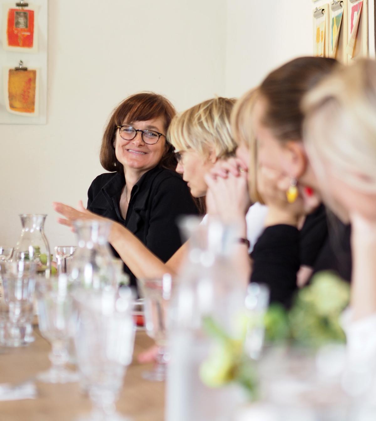 Ihmisiä pöydän ääressä, pöydällä laseja ja pulloja.