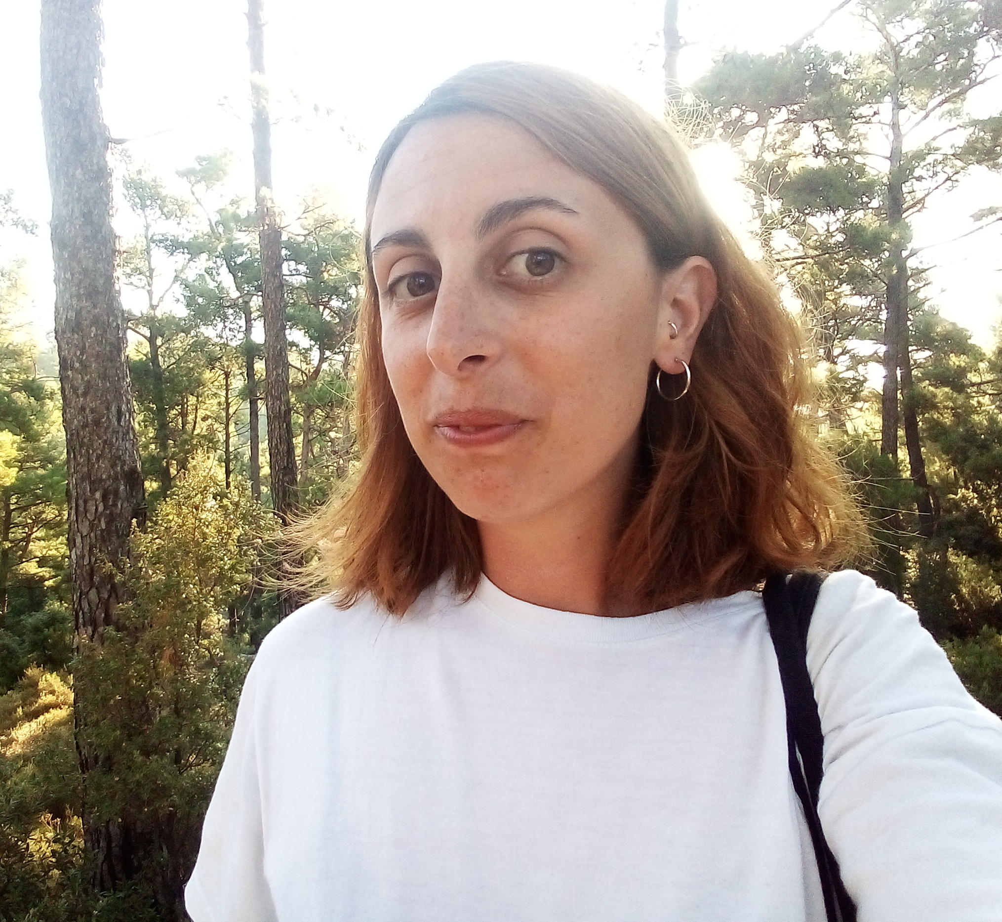 Caterina Avataneo is looking into the camera and smiling. She is in a forest and it's sunny. She is wearing a white t-shirt and has orange and brown shoulder-length hair.