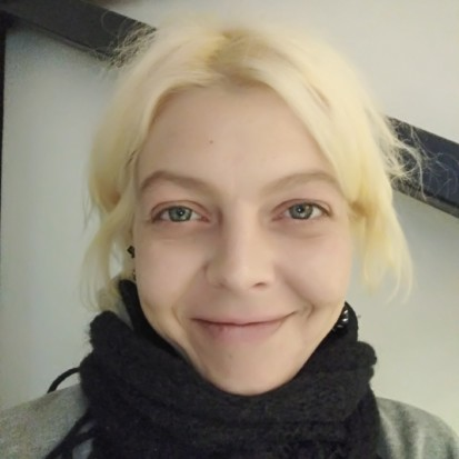 A portrait of Egle. Egle is looking into the camera smiling. She has bright blonde hair and she is wearing a black scarf around her neck.