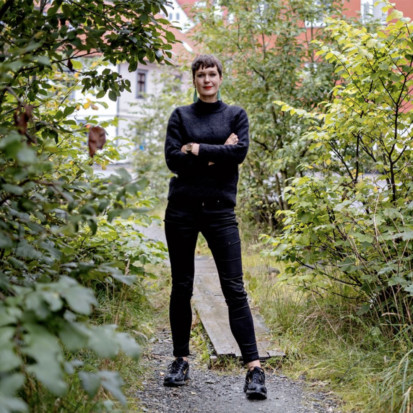 Eva Rowson is centered in the picture, where she is standing on a park path, surrounded by greenery. She is wearing black jeans and a black jumper. She is holding her arms crossed and is smiling.