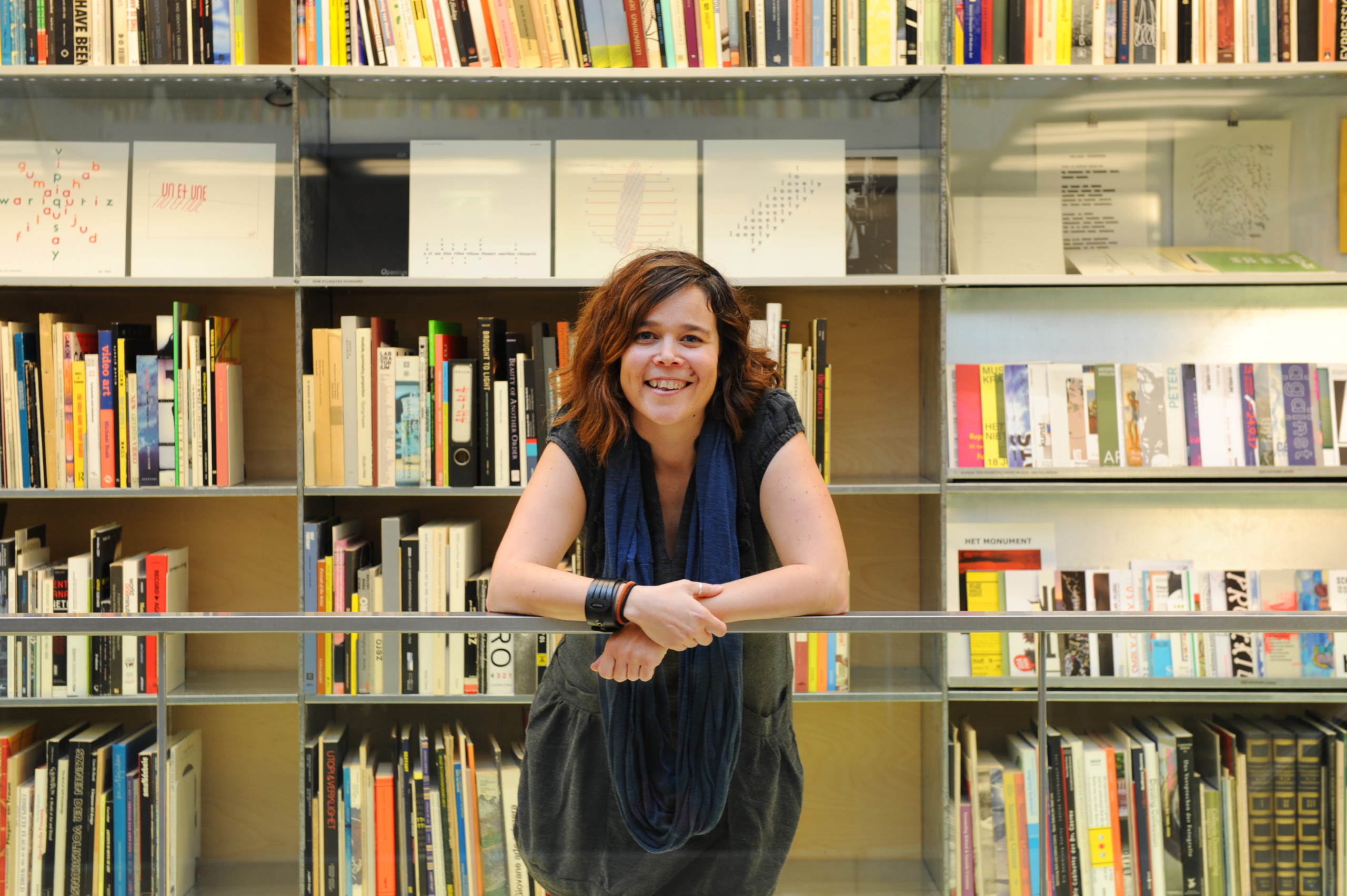 Gemma is leaning on a railing and looking into the camera smiling. She is wearing a grey dress and blue scarf and has dark hair with orange highlights. She is in front of a book shelf.