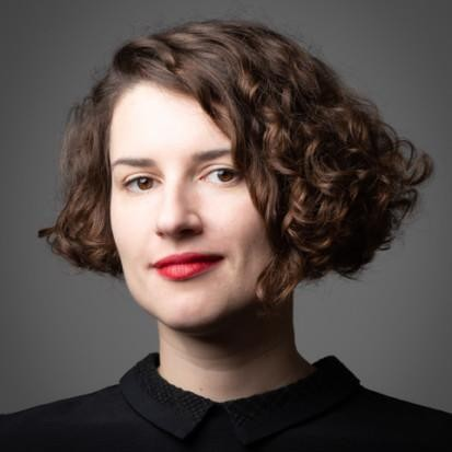 A studio portrait Miriam Wistreich in colour. She has short, brown curly hair and red lipstick. She is wearing a black collared shirt and is looking into the camera.