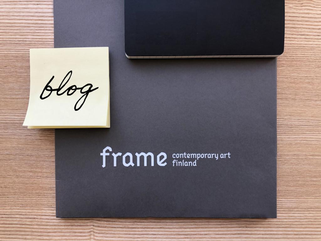 """Ett häfte, en bunt post-it lappar och ett svart papper med Frames logo ligger på ett bord i trä. Det står """"blog"""" på post-it lappen."""