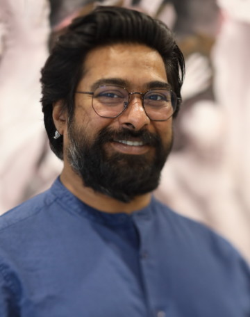 Half-portrait of Ali Akbar Mehta wearing round glasses and blue shirt with black hair and black beard. Ali looks straight into camera, smiling.