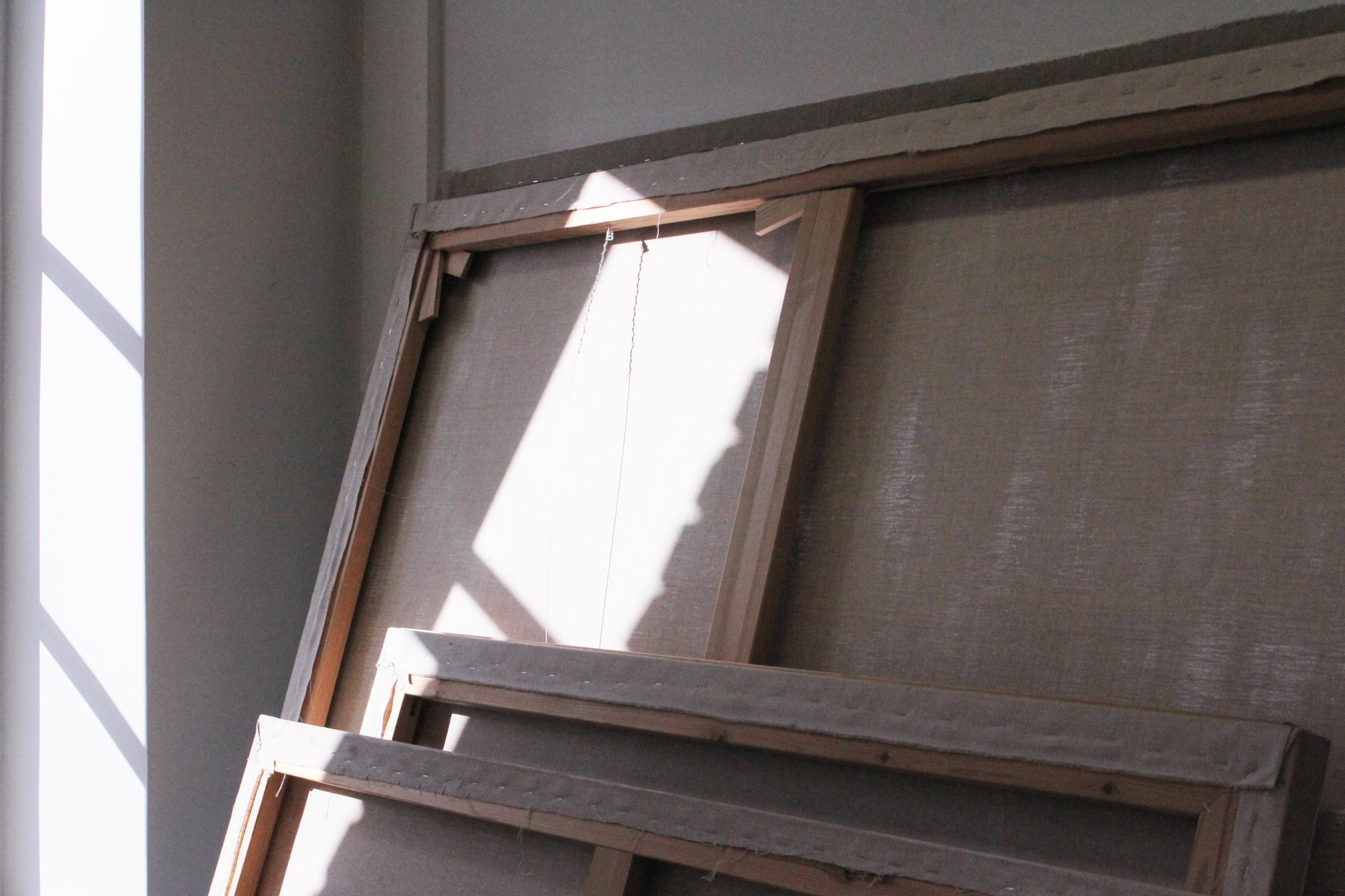 kangas kehykseen pingoitettuna taiteilijan tyohuoneella. Auringonvalo tulee ikkunasta.