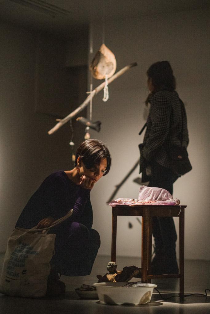 Himmeästi valaistu tila, jossa kaksi henkilö tutkii taideteosta.