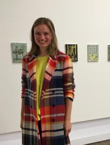 Puolipotretti Katia Krupennikovasta. Katialla pitkät hiukset, ruudullinen paita ja hän seisoo näyttelytilassa, jossa taustalla pieniä teoksia seinälle ripustettuna.