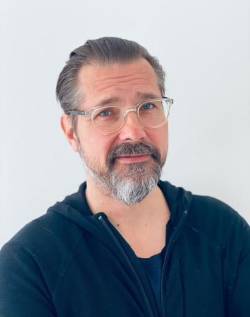 Kuva Esa Alanteesta. Hänellä on kuvassa silmälasit, parta ja sininen paita. Hän katsoon suoraan kameraan.