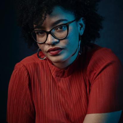 Framen fellowship-ohjelman kuraattori Ama Josephine Budge. Amalla on mustat hiukset, silmälasit ja punainen paita.