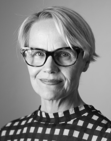 Black and white portrait of Raija Koli, the director of Frame. She has short blonde hair and she has eyeglasses with dark frames. She is smiling and looking into the camera,