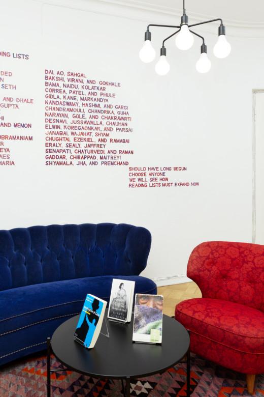 Huone, jossa punainen nojatuoli ja sininen sohva. Mustalla kahvipöydällä kirjoja. Seinällä Vihda Saumya Reading List -seinämaalaus, jossa lueteltuna Intian alueelta olevia kirjoittajia, joiden tulisi olla taiteilijan mukaan kaikkien tiedossa.