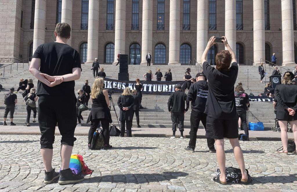 Mielenosoitus ulkona, ihmisiä turvaväein selkä kameraan päin.