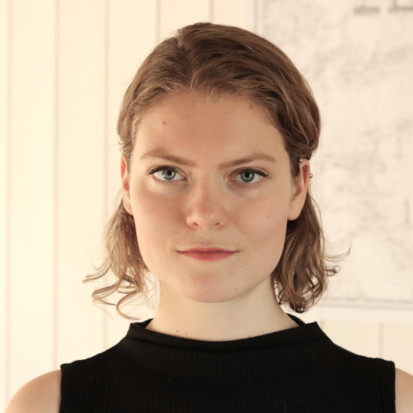 Ann Mirjam Vaikla, a white-skinned person with red lipstick and shoulder-length, curly blonde hair. Framed from shoulders up Ann Mirjam is standing in front of a white backdrop.