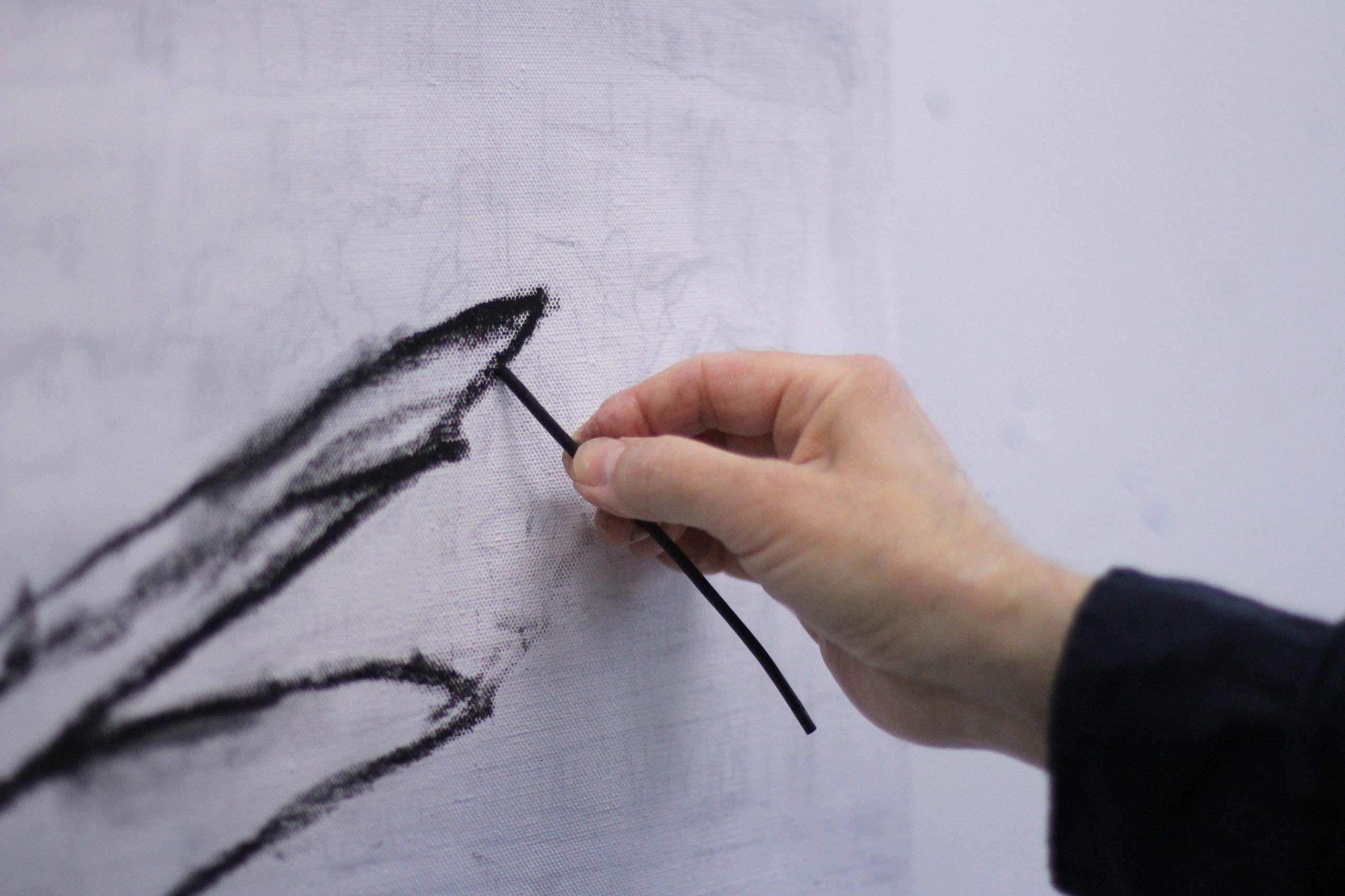 Kuvassa näkyy taiteilijan käsi, joka pitelee hiiltä. Hiilellä piirretään viivaa valkoiselle kankaalle.