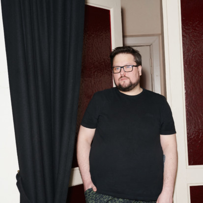 Edvinas Grinkevičius, a white-skinned person with dark brown short hair, dark brown beard, eyeglasses. Framed from knees up, Edvinas is wearing a black t-shirt, dark jeans and is leaning towards a door opening. A black curtain is on the left of Edvinas.