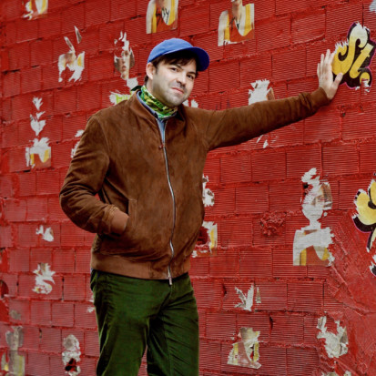 Portrait of Francisco Martínez. Francisco has short dark hair, green trousers, brown jacket, a colorful scarf and a blue cap on. Francisco is leaning with his left hand against a red wall.
