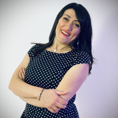 Portrait of Abir Boukhari. Abir has a long black hair and a black dress with white dots. Abir is smiling while crossing her hands. The background is white.