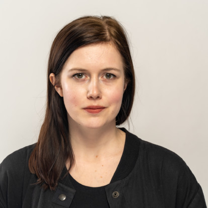 Kaarin Kivirähk, a white-skinned person with long dark brown hair and dark red lipstick. Framed from chest up, Kaarin is wearing a black shirt and a black sweater. Kaarin is standing in front of a white backdrop.