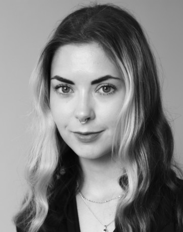 Porträtt av Laura Jurmu. Laura har långt ljusbrunt hår över axlarna och en svart skjorta. Laura ler på bilden.