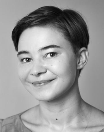 Personporträtt av Vilma Leminen. Vilma har kort mörkt som hen kammat bakåt. Vilma ler på bilden.