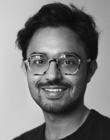 Porträtt av Reishabh Kailey. Reishabh har mörkt kort hår, mustasch och glasögon. Reishabh har en svart skjorta och ler på bilden.