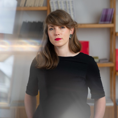 Andra Silapētere, a white-skinned person with a brown long hair, forelock and red lipstick. Framed from lower waist up Andra is standing in front of a bookshelf with her hands in her pockets.