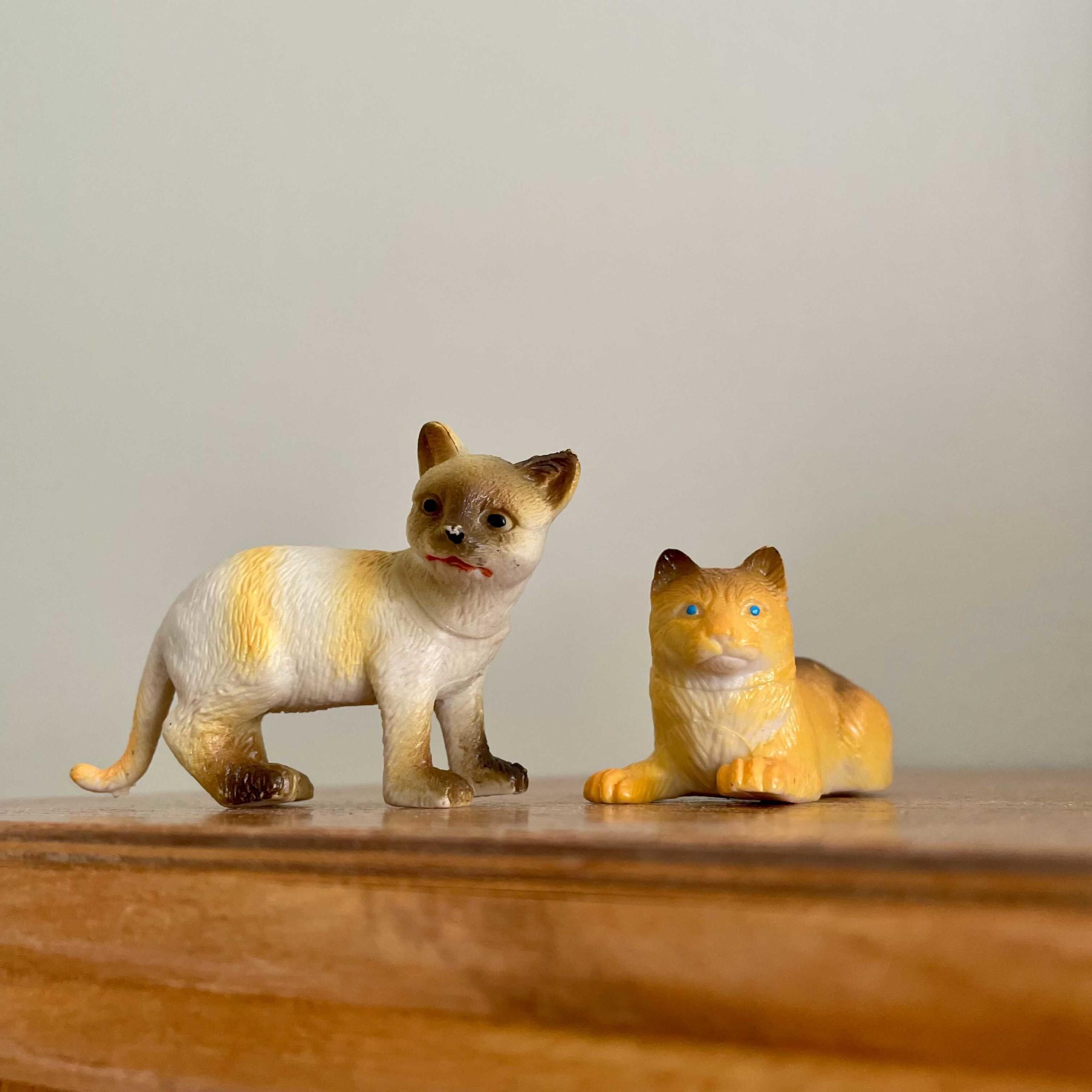 Kuvassa on vaaleaa taustaa vasten kaksi kissafiguuria ruskealla pöydällä. Toinen kissa seisoo ja toinen makoilee.