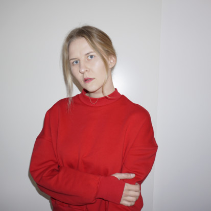 Lilian Hiob, a white-skinned person with blonde hair and red lipstick. Framed from waist up, Lilian is wearing a bright red sweater. Lilian has crossed her hands and is standing in front of a white backdrop.
